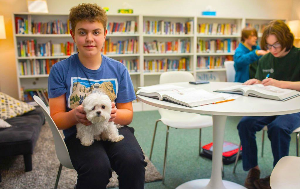 Vanguard Middle School student enjoys time with one of the school's emotional support dogs. Pets can be great companions and reduce stress levels and anxiety.